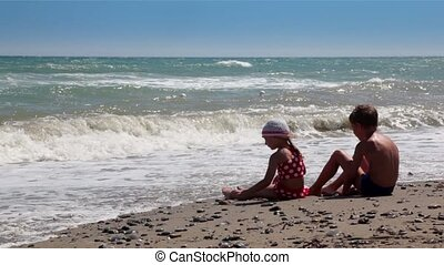 Two children, a boy and a girl, looking at the waves and throw rocks into the water, sitting in front of the water