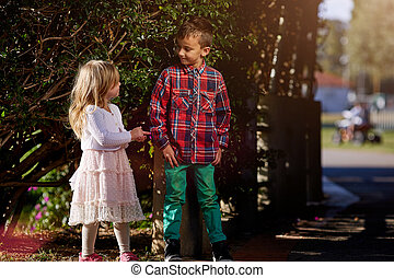 Two children, a boy and girl brother sister in autumn park walking in the woods having fun together go hand