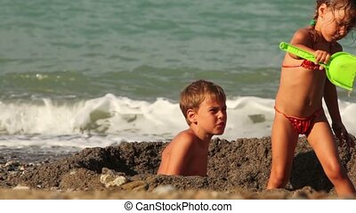 Two children are in a small pit in the sand before the water