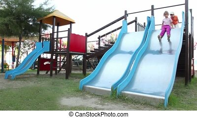 Two children are on playground object, both slide down