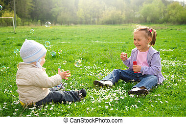 Two children are sitting on green meadow