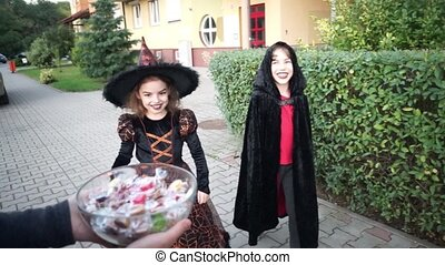 Two children, boy and girl, in dark costumes for Halloween take candies.