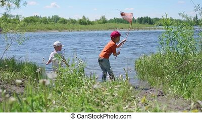 Two children catch fish on the river Bank. Beautiful summer landscape. Outdoor recreation.