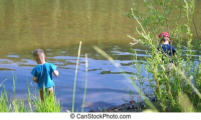 Two children catch fish with fishing rods on the river Bank. Beautiful summer landscape. Outdoor recreation.