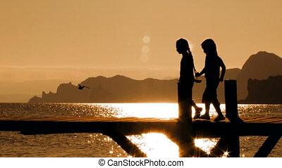 Two Children Dancing On Bridge At Sunset