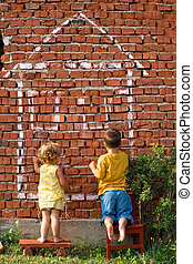 Two children drawing fantasy home on a brick wall - real estate concept