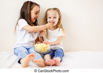 Two children eat popcorn against the white background