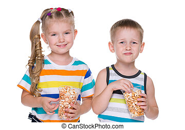 Two children eat popcorn