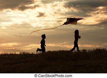 Two children enjoy flying a kite during sunset.