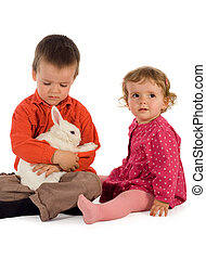 Two children getting acquainted with a bunny