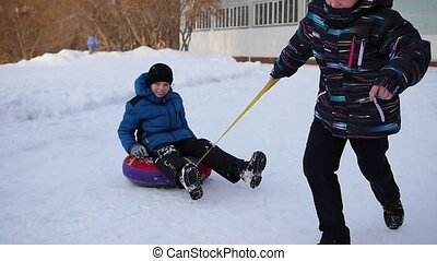 Two children have fun playing on snowtube spinning in a circle. Slowmotion