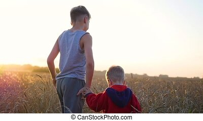 Two children holding hands walking on wheat field. Sunset