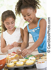 Two children in kitchen decorating cookies smiling