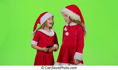 Two children in New Year costumes do selfie on the phone. Green screen. Slow motion