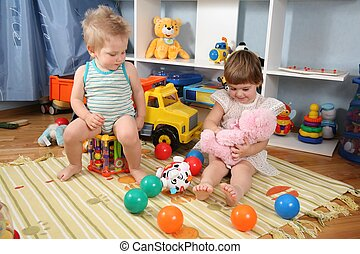 two children in playroom with toys 2