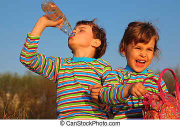 Two children in striped T-shirts,  boy drinks from  bottle,  girl holds bag