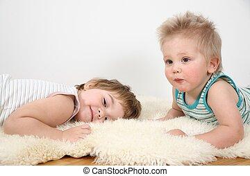 two children lie on fur carpet