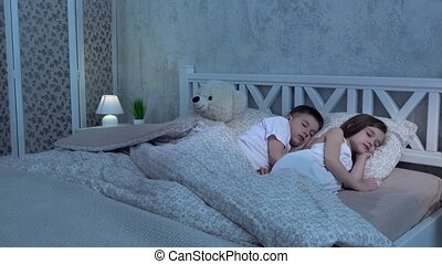 Two children lie on the bed and sleep - Two small children...