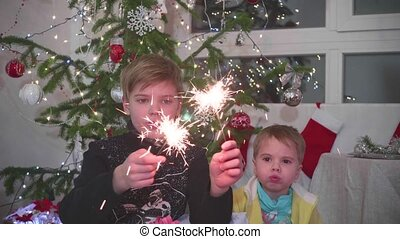 two children lit sparklers . In the background of bokeh...