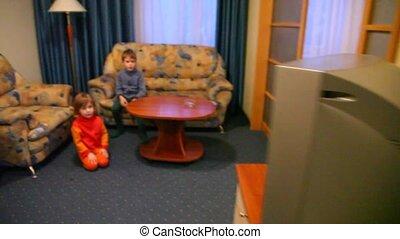 Two children look TV