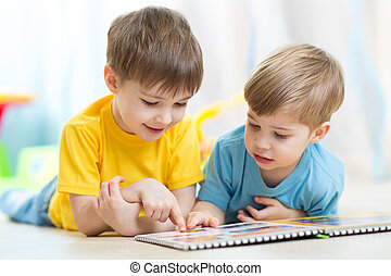 two children looking at book in playschool or nursery