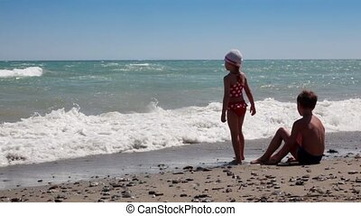 Two children looking at the waves while sitting in front of the water