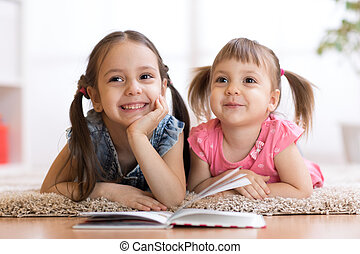 Two children lying on floor and reading book