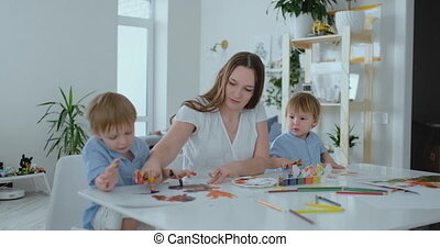 Two children of boys and mother are engaged in creative...