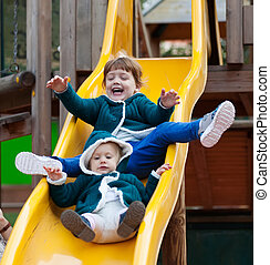 two children on slide at playground