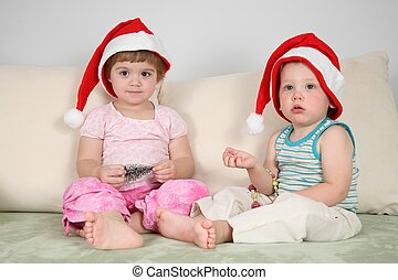 two children on sofa in santa claus hats