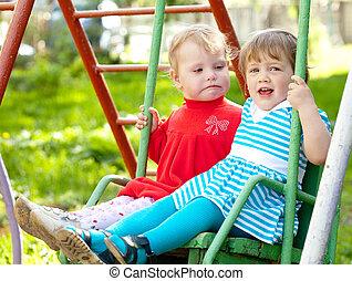 two children on swing