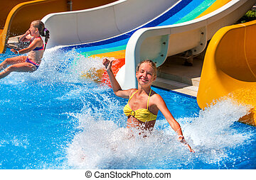 Two children on water slide at aquapark.