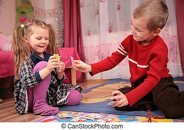 two children play cards in playroom