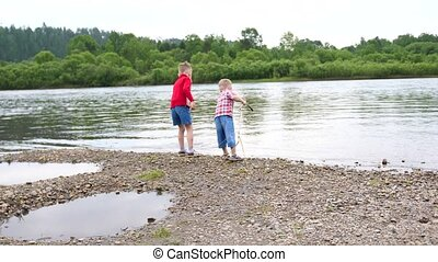 Two children play on the river Bank. Throw stones, make splashes of water. Beautiful summer landscape.