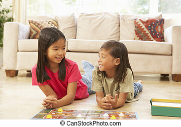 Two Children Playing Board Game At Home