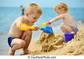 Two children playing with sand at ocean beach