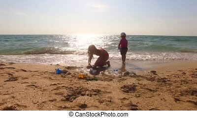 Two Children Playing With Sand On The Beach
