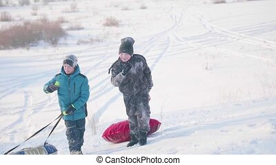 Two children ride on a snowy hill on a sled. Children climb to the top of the mountain. Walks in the fresh air