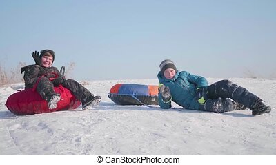 Two children ride on a snowy hill on a sled. Children sit on top of the mountain. Sport and outdoor activities