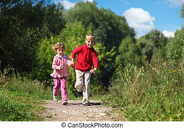two children run on path in summer