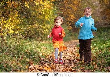 Two children run on wood autumn footpath