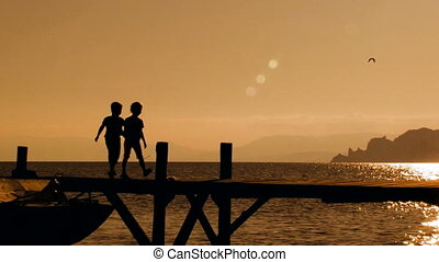 Two Children Running On Bridge At Sunset