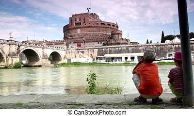 Two children sitting and look at the Sant Angelo Bridge and...