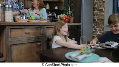 Two Children Sitting At Kitchen Table Watch Funny Video While Mother And Father Cooking, Happy Family Together At Home