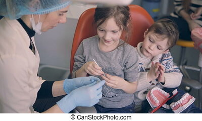 Two children sitting in dentist chair before the dental check-up. Brother and sister mould with young doctor.