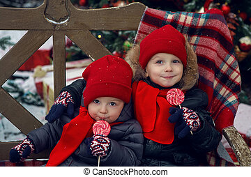 two children sitting on a bench with candy