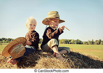 Two Children Sitting on Hay Bale in Autumn - Two young kids...