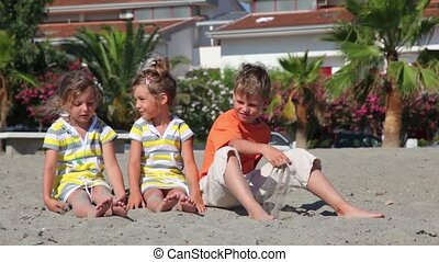 Two children sitting on the sand and throw them against the house