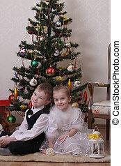 Two children sitting under Christmas tree