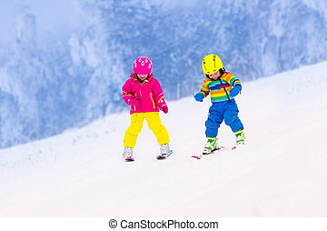 Two children skiing in snowy mountains - Children skiing in...